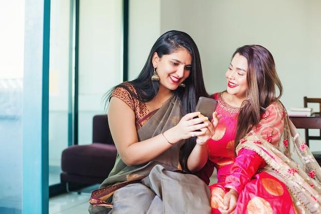 Belles femmes indiennes en sari et robe ethnique utilisant un téléphone portable à la maison