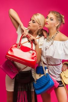 Belles femmes sur mur rose. les femelles entourées de sacs à main colorés et de sacs et de chaussures.