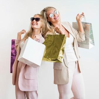 Belles femmes posant avec des sacs à provisions
