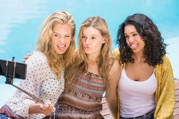 Belles femmes prenant un selfie au bord de la piscine