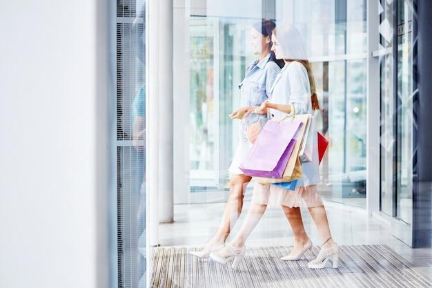Belles femmes quittant le centre commercial avec des sacs