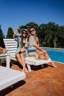 Belles femmes de race blanche prenant un selfie près de la piscine