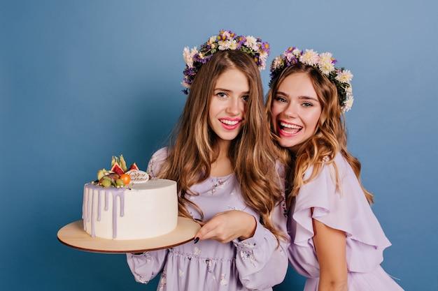 Belles femmes en robes violettes debout sur un mur bleu avec un gros gâteau crémeux