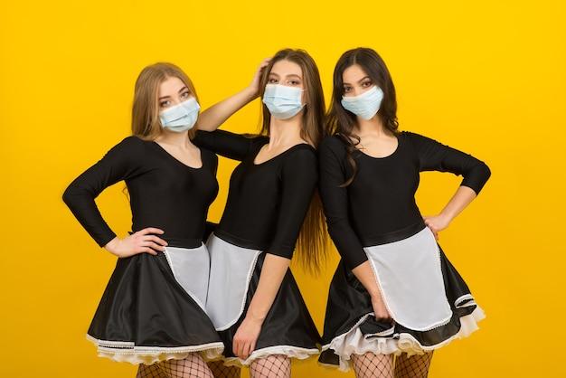 Belles femmes sexy en vêtements de femme de chambre posant en studio dans un masque de protection covid