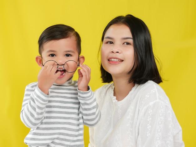 Belles femmes et son fils avec amour ensemble sur fond jaune.