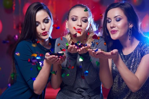 Belles femmes soufflant des confettis devant la caméra