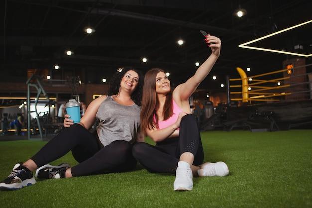 Belles femmes sportives de taille plus faisant un selfie au gymnase