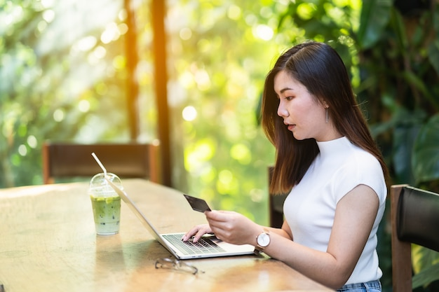 Belles femmes utilisant une carte de crédit et un ordinateur portable pour faire des achats en ligne