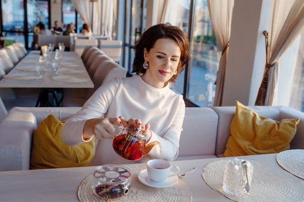 De belles femmes versent le thé d'une théière transparente dans une tasse blanche. photo de mode de vie lumineuse du petit déjeuner dans un café élégant.