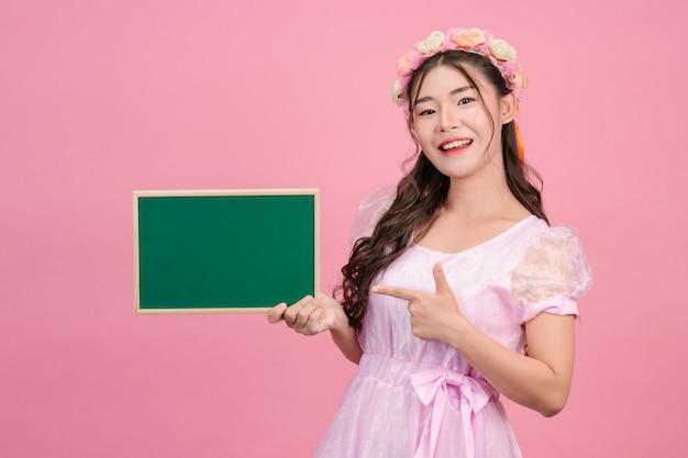 De belles femmes vêtues de robes de princesse roses tiennent un tableau vert sur un rose.