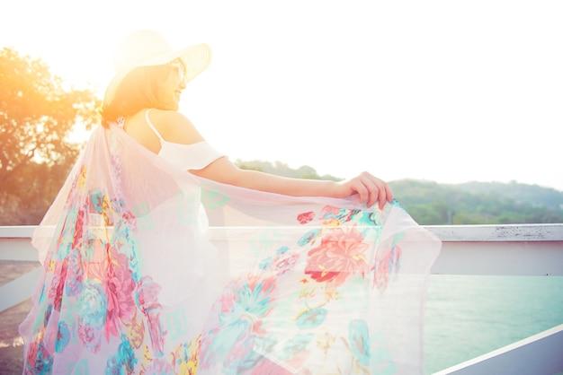 De belles femmes voyagent seules à la plage en été. mer et ciel au coucher du soleil
