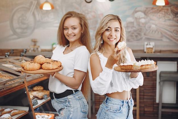 De belles filles achètent des petits pains à la boulangerie