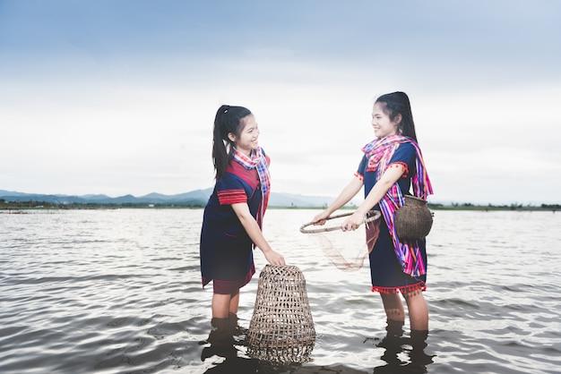 Belles filles asiatiques pêchant dans le lac avec un piège à poisson. style de vie des gens dans la campagne de la thaïlande