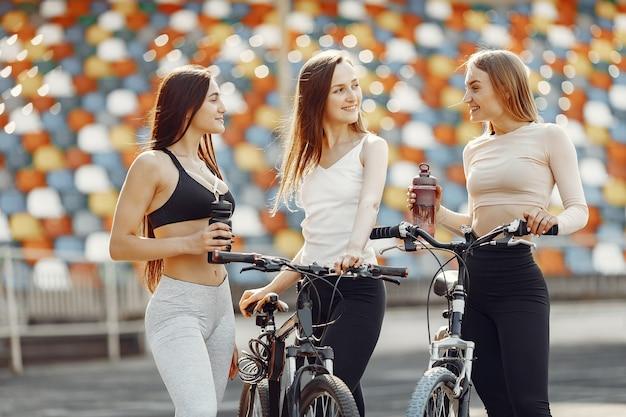 Belles filles au stade. filles de sport dans un vêtement de sport. les gens avec un vélo.