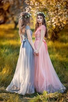 Belles filles dans un jardin de fleurs au printemps