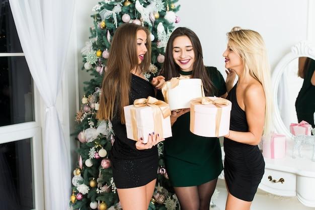 Belles filles dans la salle de noël décorée avec des boîtes-cadeaux. concept de noël et du nouvel an.