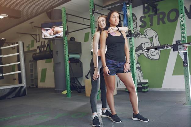 Belles filles dans une salle de sport. dames de sport dans un vêtement de sport. formation d'amis