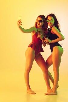 Belles filles en maillot de bain à la mode isolées sur fond jaune studio en été néon