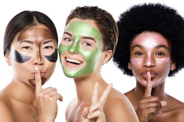 Belles filles multiethniques avec des masques peel-off colorés sur leurs visages