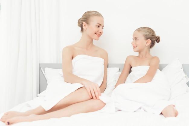 De belles filles ont eu une journée de spa. ils ont des serviettes de bain blanches.