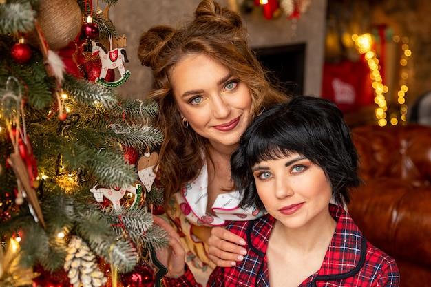 Belles filles près de l'arbre de noël filles célébrant les vacances d'hiver dans leur maison décorée