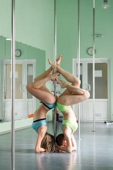 Belles filles avec un pylône, des danseuses de pole dance sur un poteau.