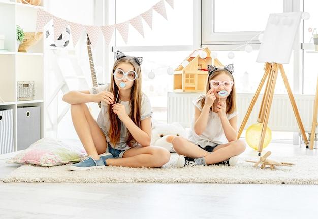 Belles filles s'amusant avec des lunettes et des lèvres sur des bâtons dans la salle de jeux