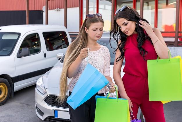 Belles filles avec des sacs sur place de parking
