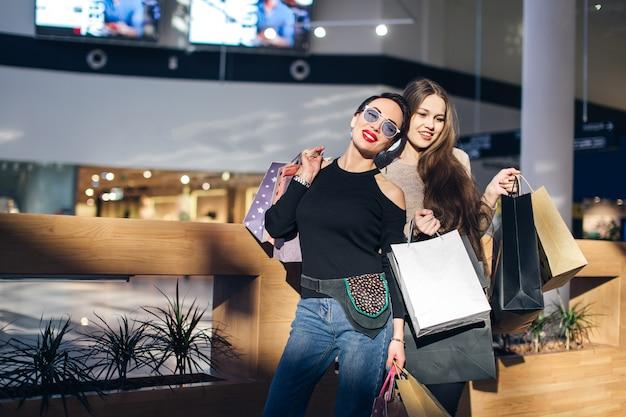 Belles filles avec des sacs à provisions regardent la caméra et sourient en faisant du shopping dans le centre commercial