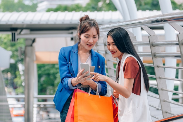 Belles filles avec des sacs à provisions sourient tout en faisant du shopping dans le centre commercial