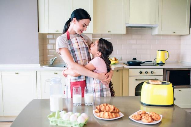 De belles filles se regardent et sourient. ils s'étreignent. les filles sont debout près de la table avec une nourriture différente. ils sont à la cuisine.