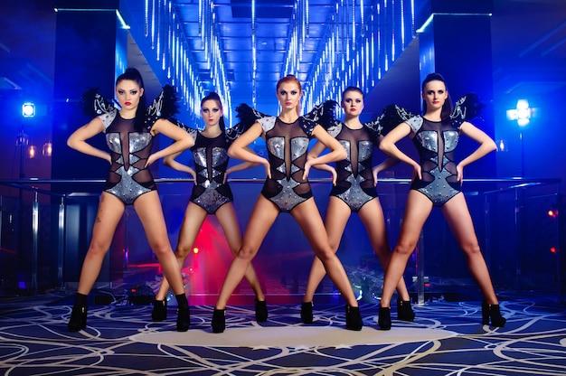 Belles filles sexy danseuse go-go posant dans la discothèque