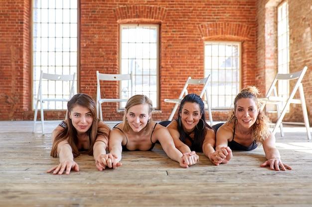 De belles filles sont allongées sur le sol et regardent la caméra. le concept est l'amitié féminine, la beauté et le succès. compagnons féminins dans la salle de gym au repos après la remise en forme, intérieur pleine longueur.