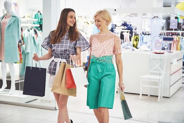Belles filles tenant des sacs à provisions et souriant tout en se tenant au centre commercial