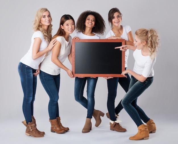 Belles filles tenant un tableau noir vide