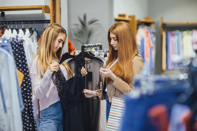 De belles filles en tenue décontractée choisissent une robe et sourient en faisant du shopping dans le centre commercial.