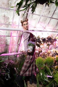 Belles fleurs. belle jolie femme tenant un pot de fleur tout en étant dans la serre