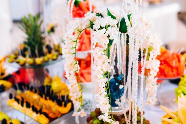 Belles fleurs blanches dans un vase de fruits en tranches sur la réception de mariage se bouchent
