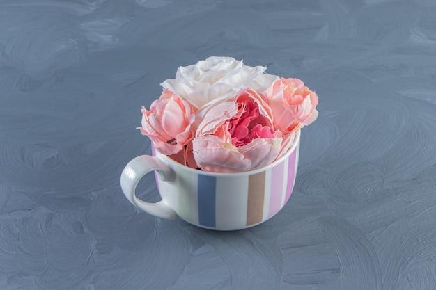 Belles fleurs dans une tasse, sur fond blanc. photo de haute qualité
