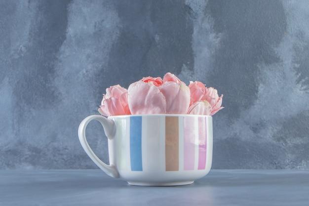 Belles fleurs dans une tasse, sur le tableau blanc.