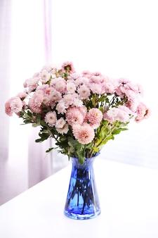 Belles fleurs dans un vase avec la lumière de la fenêtre