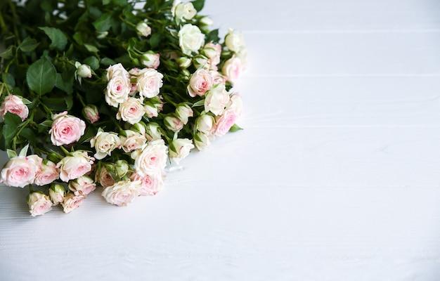 Belles fleurs sur fond blanc. bouquet de roses. pose à plat parfaite. carte postale de vacances de mère heureuse. salutation de la journée internationale de la femme. idée élégante pour la publicité ou la promotion.