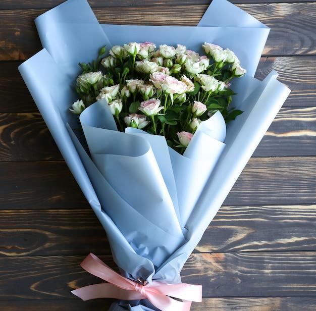 Belles fleurs sur fond en bois. bouquet de roses. pose à plat parfaite avec des pétales. carte postale de vacances de mère heureuse. salutation de la journée internationale de la femme. idée élégante pour la publicité ou la promotion.