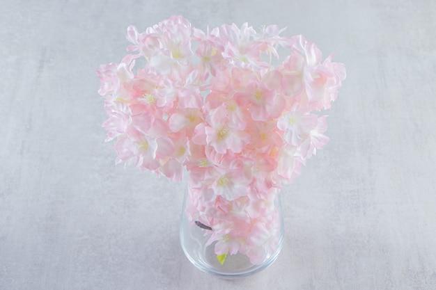 Belles fleurs fraîches de parfum dans une cruche, sur la table blanche