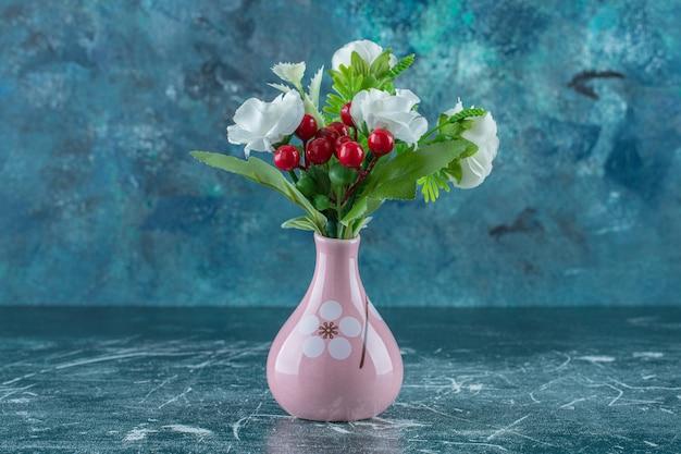 Belles fleurs parfumées et vase, sur fond bleu.