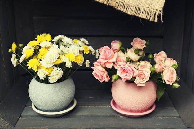 Belles fleurs en pots dans une caisse en bois
