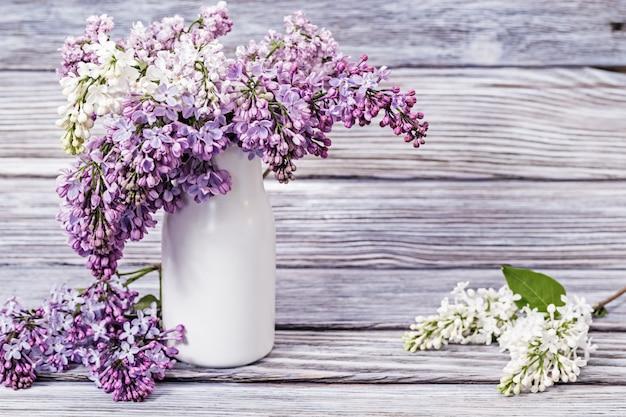 Belles fleurs printanières de lilas dans un vase sur bois avec espace de copie