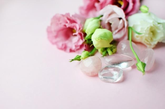 Belles fleurs roses d'eustoma (lisianthus) en pleine floraison avec du quartz rose et du cristal de roche. bouquet de fleurs sur fond blanc