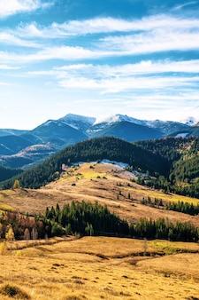 Belles forêts colorées couvrant les montagnes des carpates et un petit village sur fond de ciel d'automne chaud