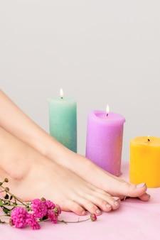 Belles jambes féminines aux pieds nus décorées de bougies allumées et de fleurs sur fond blanc.